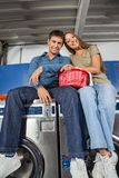 Couple With Laundry Basket Sitting On Washing Stock Photo
