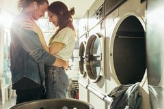 Intimate couple standing in laundry room royalty free stock photography
