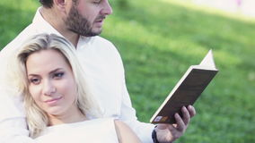 Couple on lawn reading stock video footage