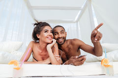 Couple laying on the beach bed and pointing finger away Royalty Free Stock Photo