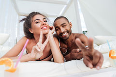 Couple laying on the beach bed and showing victory sign. Young smiling happy couple laying on the beach bed and showing victory sign outdoors Stock Photography