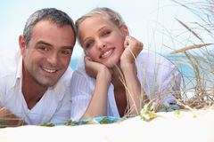 Couple laying on a beach Royalty Free Stock Photos