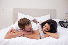 Couple laying on the bed looking at each other Stock Photo