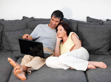Couple laying on couch with laptop Stock Photo