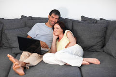 Couple laying on couch with laptop Royalty Free Stock Images