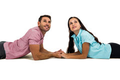 Couple laying on the floor face to face holding hands and looking up Royalty Free Stock Image