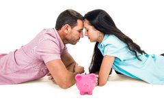 Couple laying on the floor face to face with piggybank Stock Images