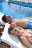 Couple laying on lounge chairs with eyes closed at poolside Stock Image
