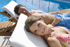 Couple laying on lounge chairs at poolside Royalty Free Stock Image