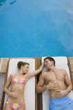 Couple laying on lounge chairs at poolside Stock Photography