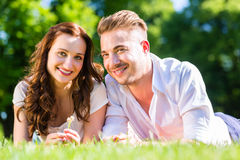 Couple laying on park lawn enjoying Stock Photos