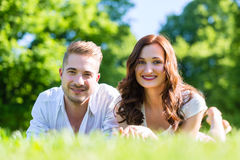 Couple laying on park lawn enjoying Royalty Free Stock Photos