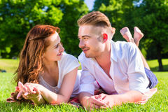 Couple laying on park lawn enjoying sun Royalty Free Stock Image