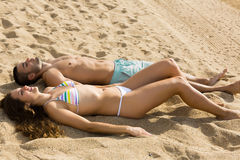 Couple laying on sandy beach  in sunny day Stock Image