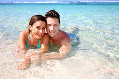 Couple laying in sea water Stock Image