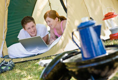 Couple laying in tent with laptop Royalty Free Stock Photos
