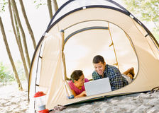 Couple laying in tent using laptop Stock Photos