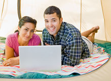 Couple laying in tent using laptop Royalty Free Stock Photo