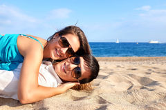 Couple laying together on beach. Stock Images
