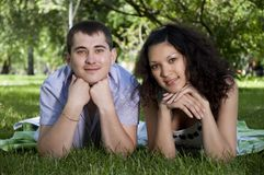 Couple lays together on a grass Stock Images
