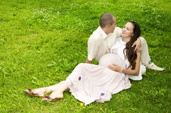 Couple lays together, hugging, pregnant woman. Man and the woman lay together on cover,  smiling pregnant woman Royalty Free Stock Photography