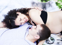 Couple lays together, hugging, pregnant woman Royalty Free Stock Photos