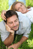 Couple lazing in the grass. On a Sunday Royalty Free Stock Image