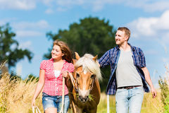 Couple leading horse thru meadow Royalty Free Stock Photos
