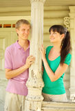 Couple leaned to column, smile on terrace Royalty Free Stock Photos
