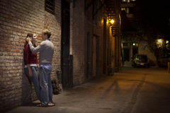 Couple leaning against brick wall in alley way Stock Photo