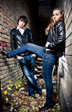 Couple leaning against brick wall at lane at night Royalty Free Stock Photography
