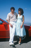A couple leaning against a red car in Los Angeles, CA Royalty Free Stock Photo
