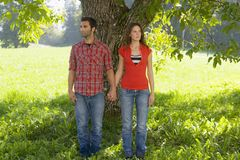 A couple leaning against a tree. Royalty Free Stock Photos