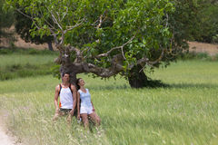 Couple leaning against tree in rural field stock images