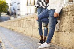 Couple leaning against a wall in Ibiza, Spain, low section Royalty Free Stock Photo