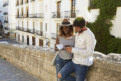 Couple leaning against a wall reading a guidebook, Ibiza Stock Image