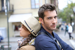 Couple leaning backs on eachother. Couple in street leaning back to back stock photography