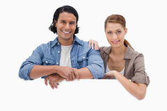 Couple leaning on blank wall Royalty Free Stock Images