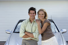 Couple leaning on bonnet of parked convertible car on driveway, smiling, front view, portrait Stock Images