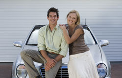 Couple leaning on bonnet of parked convertible car on driveway, smiling, front view, portrait Royalty Free Stock Images