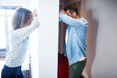 Couple leaning on opposite sides of the wall Stock Photos