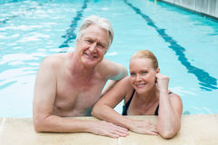 Couple leaning at poolside Stock Photos