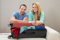 Couple leaning on suitcase. Portrait Of Happy Couple Leaning On Suitcase Royalty Free Stock Photography