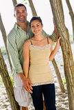 Couple leaning on tree at beach stock images