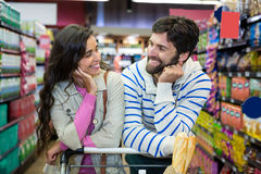 Couple leaning on trolley at supermarket. Happy couple leaning on trolley at supermarket Stock Photo