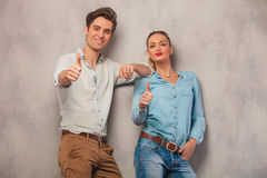 Couple leaning on a wall while showing the thumbs up Royalty Free Stock Photo
