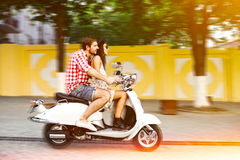 Couple learning to drive a scooter on road Royalty Free Stock Photos