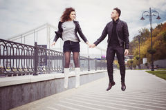Couple in leather jackets jumping on seafront on a cloudy day outdoors Stock Image