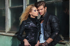 Couple in leather jackets posing against an old building