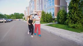 Couple leaving the building and starting to run. Morning jogging before the work. Sport and healthcare stock video